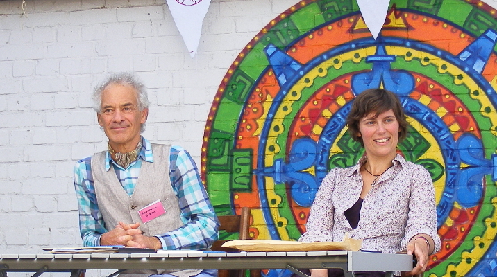 Franziska Klinkigt und Bertrand Stern sitzend vor einem riesigen Mandala auf einer Steinwand